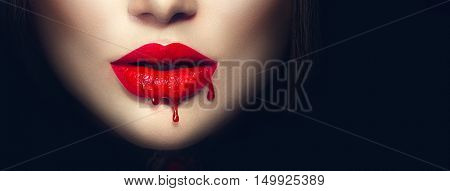 Beauty Sexy Vampire red lips with dripping blood close up. Isolated on black background.