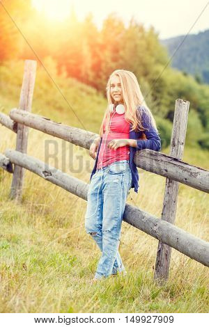 Young Stylish Girl Standing Near Fence In Hillside