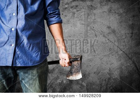 A guy holding old rusty axe, close up front view, on dark concrete texture background with copy space