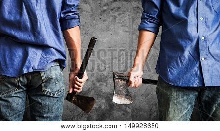 A guy holding old rusty axe, on dark concrete texture background