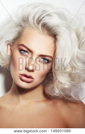Portrait of young beautiful tanned woman with stylish make-up and platinum blonde curly hair