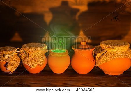 Halloween concept greeting card of clay pots with green mystical miracle light on wooden background fine art design rural style close up