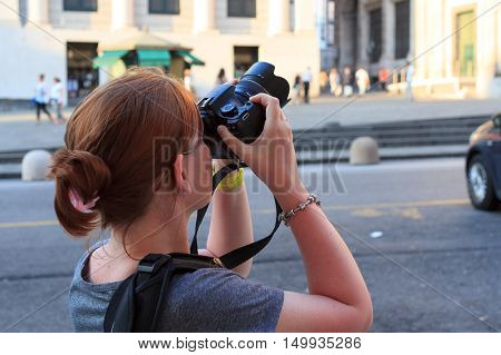 Tourist woman with camera taking picture of a tourist attraction in Genoa, Italy