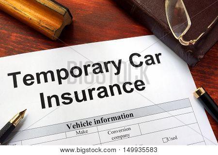 Temporary car insurance application form on a table.