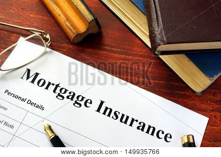Mortgage insurance policy with a book and a pen.