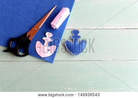 Home made anchor decor. Blue felt anchor is sewn with white thread, needle, paper pattern pinned on a flat piece of blue felt, scissors on a yellow background. Sewing lesson for children. Step