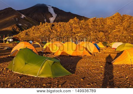 Fairy dawn National Park Landmannalaugar, Iceland. Tents tourists, mountains and glaciers covered with warm orange light