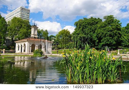 London, United Kingdom - May 14, 2014. Italian Garden fountains in the Kensington Gardens in London, with buildings, vegetation and people.
