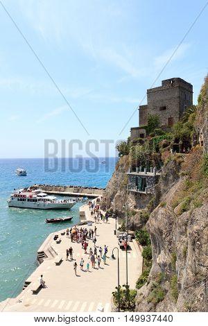 Monterosso, Italy - June 26, 2016: Port in Cinque Terre village Monterosso al Mare, Torre aurora and Mediterranean Sea. Monterosso is one of the five villages in Cinque Terre. The Torre Aurora is a famous watchtower.