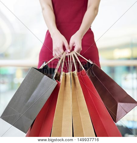 young woman female shopper standing with colorful paper bags in hands in shopping mall or department store focus on paper bags