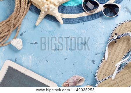 Beach vacation background. Flip-flops, sunglasses, seashells and blackboard over stone backdrop. Top view with copy space