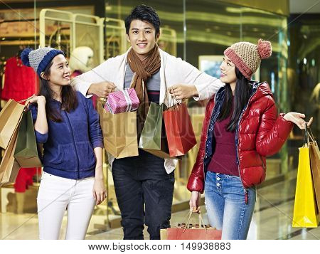young asian people friends enjoying shopping for christmas gifts in mall or department store