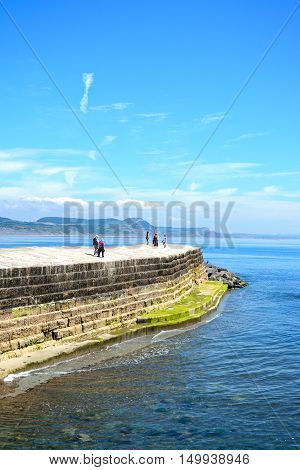 LYME REGIS, UNITED KINGDOM - JULY 18, 2016 - Holidaymakers on the harbour wall with views towards the coastline Lyme Regis Dorset England UK Western Europe, July 18, 2016.