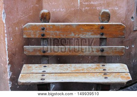 An old wooden bench against a wall