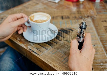 Man Holding Vape Or Electronic Cigarette And Drinking Coffee