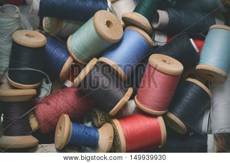 Vintage hipster background of plenty multicolor threads bobbins top view. Atelier, sewing accessories backdrop.