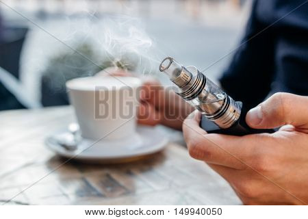 Man Using Vape Or Electronic Cigarette And Drinking Coffee