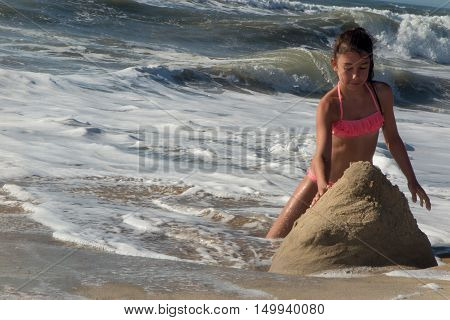 Young Girl In Bikini Playing With Sands At Sea Shore