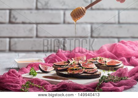 Fresh bread with figs, ricotta and honey on white cutting board