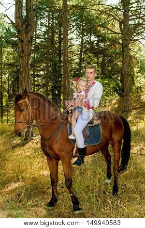 image of a young dad daughter rolls on the horse in the woods