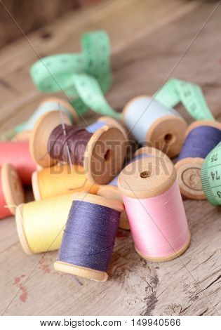 Vintage hipster background of plenty multicolor threads bobbins old wooden table. Atelier, sewing accessories backdrop.