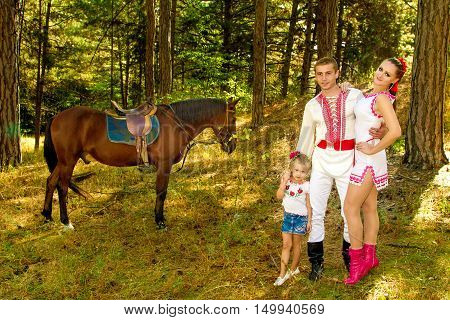 a Ukrainians Mom and Dad and daughter in the woods with a horse