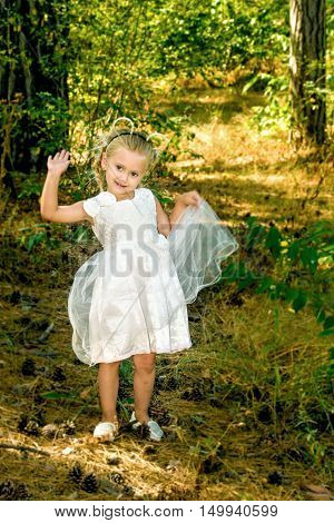 picture of little girl in a beautiful dress walks in the woods
