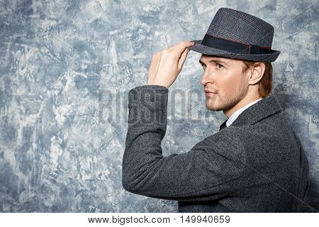 Portrait of a handsome man in an elegant coat. Beauty, fashion. Studio shot. Autumn style clothes.