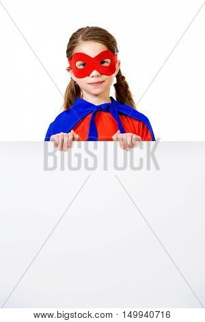 Cute girl teenager in a costume of superhero holding white billboard. Copy space. Isolated over white background.