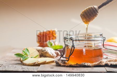 Honey in jar with honey dipper, ginger and lemon on wooden background