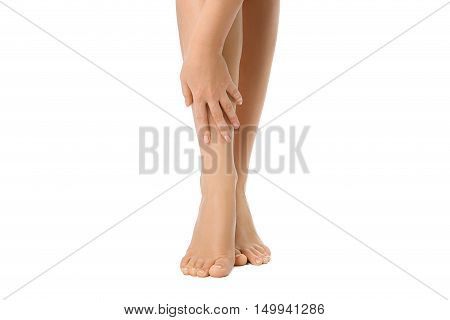 Bare legs of woman with her hand isolated on white. Beautiful skin. Foot care