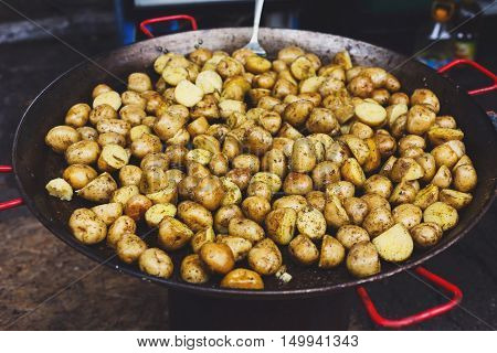 Country fair cooking. Roasted potatoes cooked outdoors in big metal cauldron pot. Cookout vegetable meals. Fresh organic, healthy snack, potatoes cooked on grill flame. Street food, fast food.