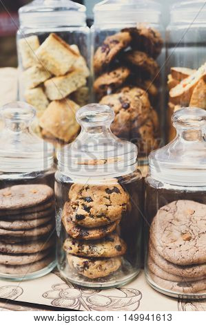 Desserts choice. Cookies and biscuits in glass jars on counter bar for sale. Chocolate drops and chips, oatmeal cookies stacks. Vertical image