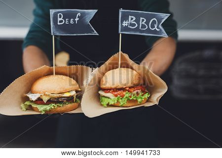 Fresh beef burgers cooked at barbecue outdoors. Cookout american bbq food with text label. Big hamburger with steak meat and vegetables closeup with chef unfocused at background. Street fast food.