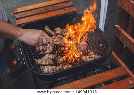 Grill steaks on metal grate with flame. Chef hands cooking roasted meat barbecue with lots of fire. BBQ fresh beef chop slices. Traditional dish on charcoal and flame, picnic, street food