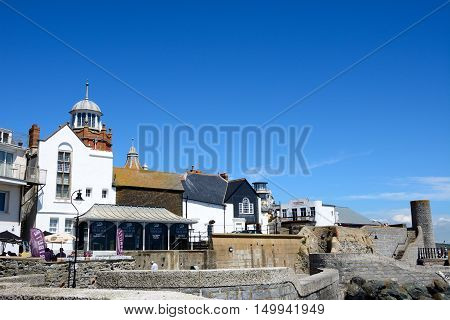 LYME REGIS, UNITED KINGDOM - JULY 18, 2016 - Seafront wall along Gun Cliff Walk with the Lyme Regis Museum and town buildings to the rear Lyme Regis Dorset England UK Western Europe, July 18, 2016.
