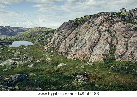 Pink granite mountain and alpine meadows in sunny day. Arctic summer the tundra Norway.