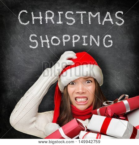 Christmas gifts shopping woman holiday stress. Stressed girl buying presents wearing red santa hat looking frustrated and distressed with funny expression on black chalkboard copyspace background.
