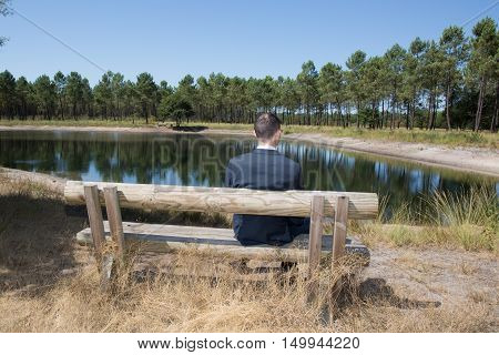 Young man sitting alone on park bench looking down to the water in late afternoon