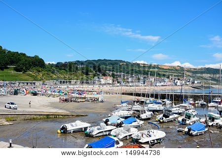 LYME REGIS, UNITED KINGDOM - JULY 18, 2016 - Boats and yachts moored in the harbour with the town and beach to the rear Lyme Regis Dorset England UK Western Europe, July 18, 2016.