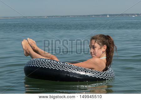 Smiling young girl in a black buoy at the ocean