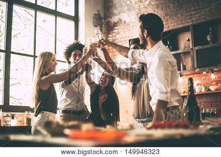 Cheers to best friends! Low angle of cheerful young people cheering with champagne flutes and looking happy while having party on the kitchen