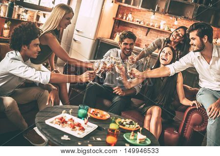 Cheers to best friends! Group of cheerful young people enjoying food and drinks while spending nice time in cofortable chairs on the kitchen together