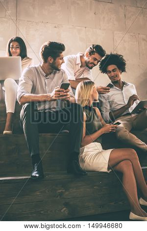 Modern students. Group of cheerful young people communicting while holding different gadgets and sitting close to each other on steps