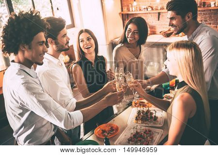 To the old friends! Top view of cheerful young people cheering with champagne flutes and looking happy while having party on the kitchen