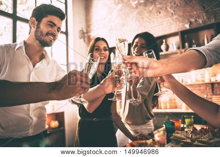 Cheers! Low angle view of cheerful young people cheering with champagne flutes and looking happy while having party on the kitchen