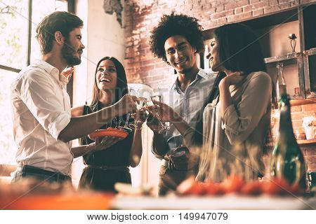 Enjoying party with friends. Low angle view of cheerful young people cheering with champagne flutes and looking happy while having home party