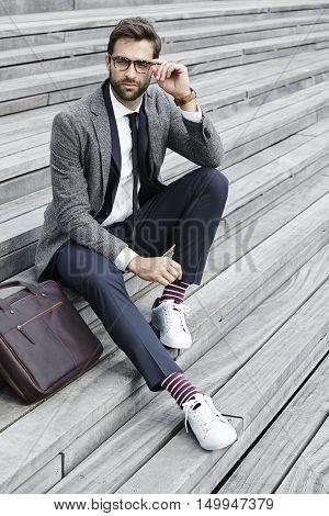 Businessman in specs on steps looking away