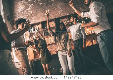 Friends dancing. Low angle view of cheerful young people dancing and drinking while enjoying home party on the kitchen