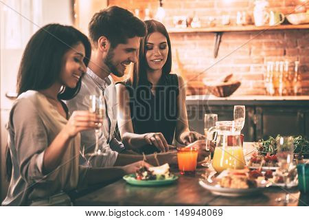 Dinner party. Cheerful young people enjoying meal while sitting at the dinning table on the kitchen together